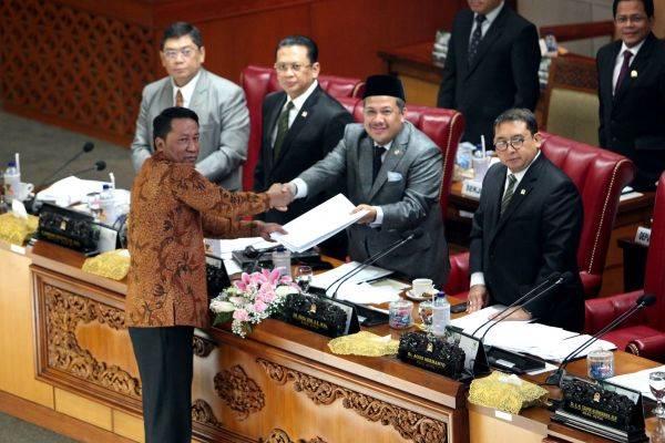 Ketua Badan Legislasi Supratman Andi Agtas (kiri) menyerahkan hasil pembahasan revisi UU KPK kepada pimpinan rapat Fahri Hamzah