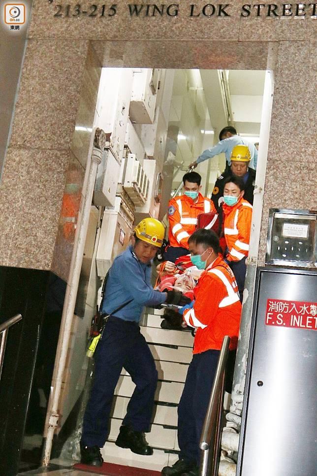 救護員將女子從5樓平台抬落路面。(沈厚錚攝)