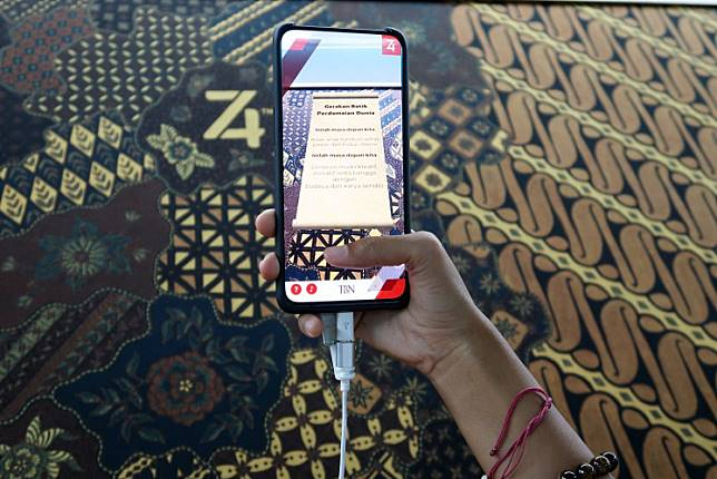"""A visitor tries batik augmented reality during the """"Menuju New York lewat MRT"""" event on Saturday."""