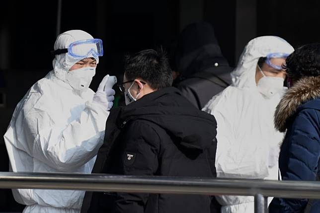 Travellers are checked by security personnel wearing hazardous material suits at the entrance to the underground train station in Beijing on Jan. 24, to help stop the spread of a deadly SARS-like virus which originated in the central city of Wuhan. China sealed off millions more people near the epicenter of a virus outbreak on January 24, shutting down public transport in an eighth city in an unprecedented quarantine effort as the death toll from the disease climbed to 25.
