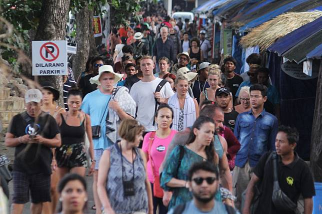Tourists walk to a pick-up point at Sanur Beach, Denpasar, after their return from Nusa Penida Island in Bali on Feb. 10.