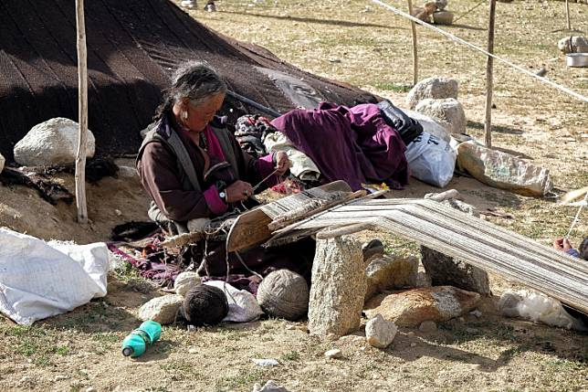 In this picture taken on August 29, 2019, a Changpa nomad looms pashmina wool in a nomadic camp, some 1 kilometer from Korzok village, in the Leh district of Ladakh.