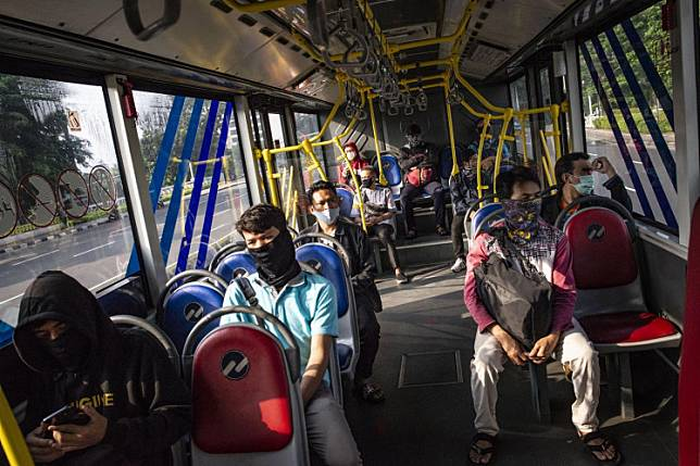 Passengers wearing masks ride a Transjakarta bus on Friday. The Jakarta administration has imposed large-scale social restrictions (PSBB) that will last for two weeks starting on Friday in a bid to control the spread of COVID-19.