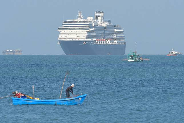The Westerdam cruise ship passes fishing boats as it approaches the port in Sihanoukville, Cambodia, on Thursday, where the liner had received permission to dock after being refused entry at other Asian ports due to fears over the coronavirus outbreak.