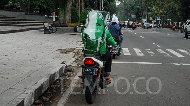 An online ojek driver equipped with a protective screen awaits would-be passengers on his bike in Bandung, West Java, Monday, June 8, 2020. TEMPO/Prima Mulia
