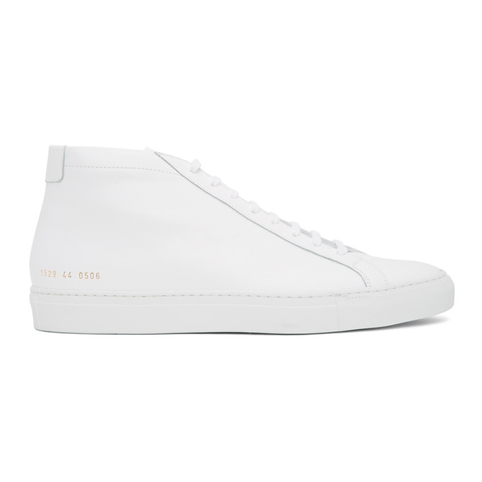 Mid-top buffed leather sneakers in white. Round toe. Tonal lace-up closure. Padded tongue and collar