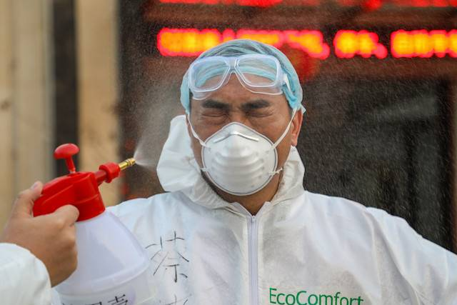 This photo taken on Feb. 3, shows a doctor being disinfected by his colleague at a quarantine zone in Wuhan, the epicenter of the new coronavirus outbreak, in China's central Hubei province. Liu Zhiming, the director of Wuchang Hospital in Wuhan, died Tuesday morning after