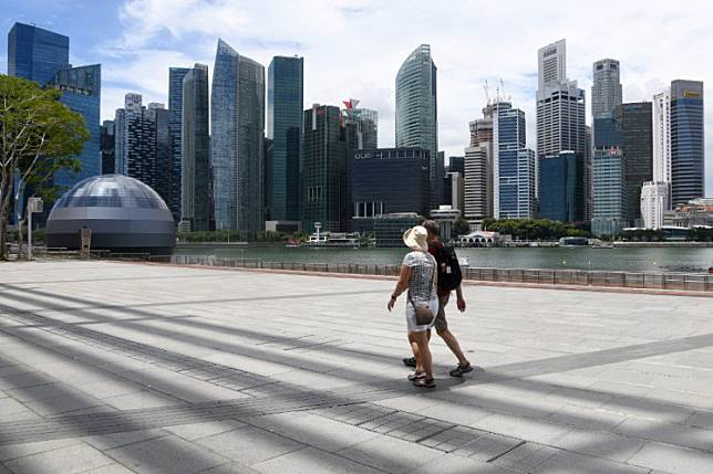 Visitors walk along a walkway at Marina Bay in Singapore on Feb.18, 2020. A Chinese national who contracted coronavirus has been charged by Singaporean authorities for allegedly giving false information about his whereabouts in the city-state and could face up to six months in jail.