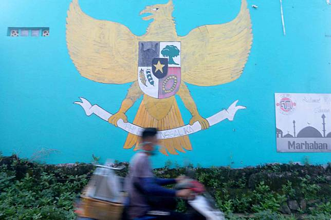 Happy birthday, Pancasila: A motorcyclist passes a Garuda Pancasila mural painted on a wall on Jl. Puspitek Raya in South Tangerang, Banten. Pancasila was officially promulgated by Sukarno on June 1, 1945, but only in 2016 did Pancasila Day become a public holiday.