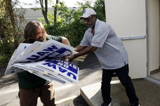 General Motors Co. employee Carl More (right) passes strike signs to Cleo Long at the United Auto Workers (UAW) Local 163 which represents GM's Romulus Powertrain on September 15, 2019 in Westland, Michigan. Local UAW leaders from across the nation met Sunday morning in Detroit after the 2015 General Motors collective bargaining agreement expired Saturday night and opted to strike at midnight on Sunday.