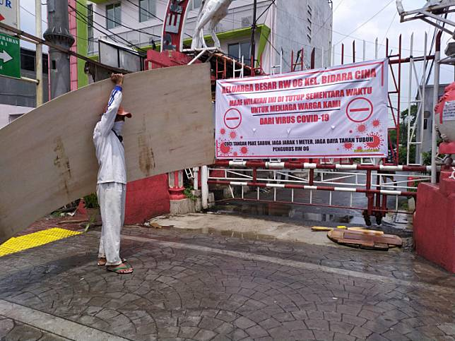 A worker carrying a plywood board passes a banner put up by Bidara Cina residents in East Jakarta on Wednesday. The banner states that the alley of the area where the residents lived is temporarily closed to prevent the spread of Covid-19.