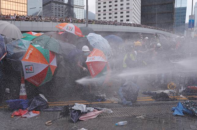 Protesters are hit by police water cannon during a demonstration against a proposed extradition bill in Hong Kong, China June 12, 2019.