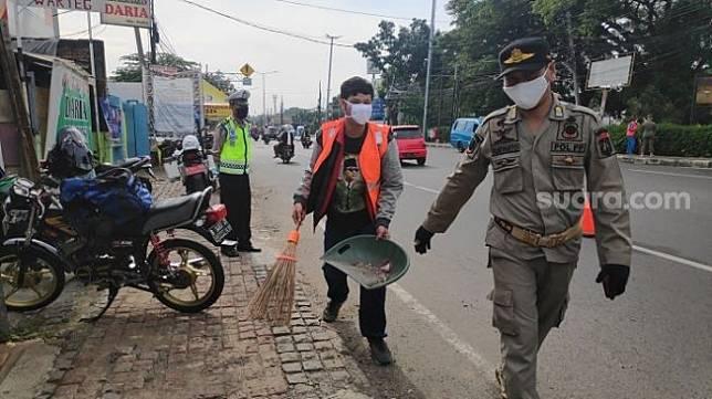 Pelanggar PSBB yang dikenakan sanksi sosial oleh petugas di check point Pasar Rebo, Jaktim. (Suara.com/Bagaskara).