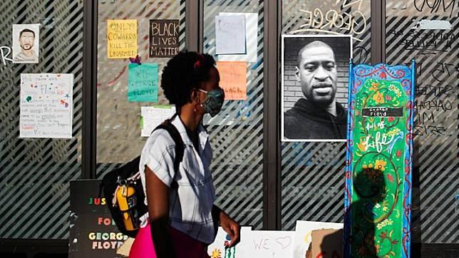 Seorang wanita melewati potret pria keturunan Afrika-Amerika, George Floyd yang dipasang saat penghormatan di sebuah halte yang dikelilingi buket bunga di Minneapolis, Minnesota, AS, 28 Mei 2020. Kematian Floyd yang mengundang kemarahan warga menimbulkan kerusuhan di Kota Minneapolis. REUTERS/Carlos Barria