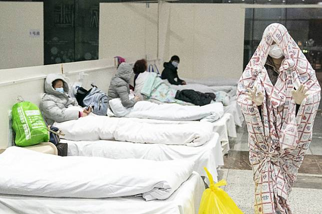This photo taken on Feb. 5, 2020 shows a patient (right) covered with a bed sheet at an exhibition centre converted into a hospital as it starts to accept patients displaying mild symptoms of the novel coronavirus in Wuhan in China's central Hubei province.Devastated and angry Wuhan residents are now demanding answers from a government that they accused of incompetence and lying about the extent of the virus.