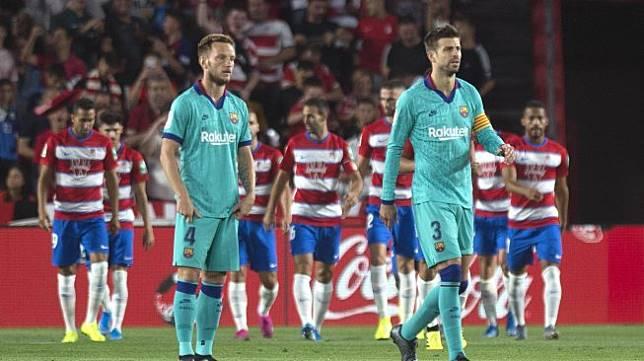 Gelandang Kroasia asal Ivan Rakitic dan bek Gerard Pique bereaksi terhadap gol gelandang Granada Ramon Azeez selama pertandingan sepak bola liga Spanyol antara Granada melawan Barcelona di Stadion Nuevo Los Carmenes, Granada, Spanyol, Minggu (22/9) dini hari WIB.  [GUERRERO JORGE / AFP]