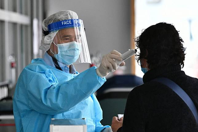 A medical worker wearing protective gear (L) takes the temperature of a woman as she enters Princess Margaret Hospital in Hong Kong on Feb. 4.Hong Kong reported its second death from the new coronavirus on Wednesday.