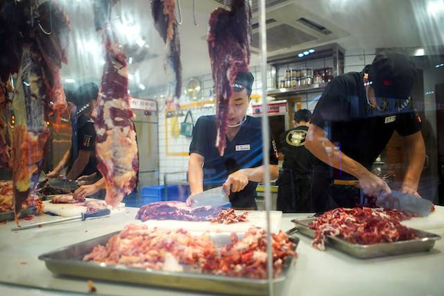 Workers cut beef at a restaurant in Shenzhen, Guangdong Province, China, Sept. 6, 2019. Shenzhen has banned the eating of dogs and cats as part of a wider clampdown on the wildlife trade since the emergence of the new coronavirus.