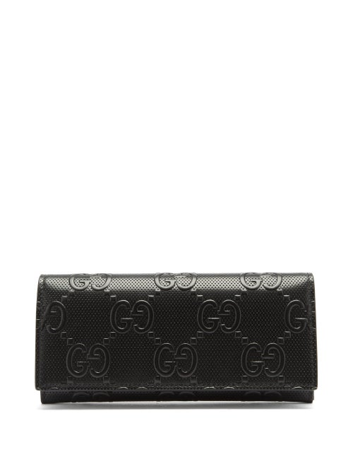 Gucci - Gucci's iconic GG logo is embossed across the smooth leather construction of this black wallet, evoking a sophisticated tone. It's crafted in Italy and opens to reveal card slots and note sleeves with a zipped coin pocket, then finished with a subtle logo along the interior.