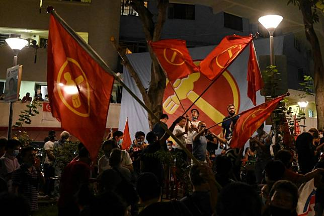Supporters of the opposition Worker's Party wave party flags as they gather in the Hougang public housing district during the counting of votes of the general election in Singapore, in the early hours of July 11, 2020. Singapore's long-ruling party is on course to retain power convincingly, but the opposition has made gains in an election held under the shadow of a coronavirus outbreak, early tallies indicated early on July 11.
