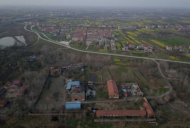 This aerial photo taken on March 7, 2020, shows houses and buildings in Hubei province across the Jiujiang Changjiang no. 2 bridge. China's Hubei province said it will allow transportation to resume for the city of Wuhan on April 8, effectively lifting a mass quarantine over the city where the coronavirus first emerged last December.