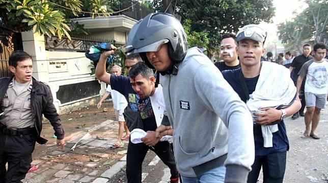 Polisi dan warga menangkap seorang yang diduga provokator pembakaran mobil di Komplek Asrama Brimob, Petamburan, Jakarta, Rabu (22/5). [Suara.com/Arief Hermawan P]
