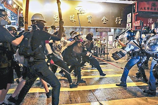 示威者持長棍及木條追打防暴警員。(美聯社圖片)