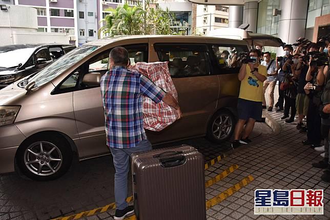 兩名男士將三大袋紅白藍腳袋及一個大行李箱放上車。
