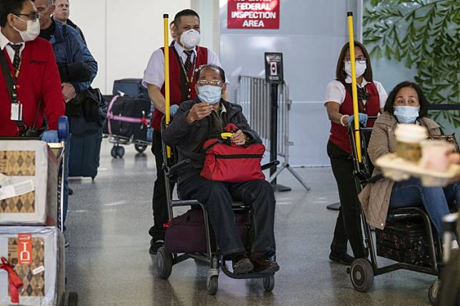 Travelers arriving from Beijing wear disposable face masks at San Francisco International Airport in San Francisco, California, U.S., on Friday, Jan. 31, 2020. The U.S. is funneling flights from China to the U.S. to seven airports to help contain spread ofcoronavirus, Health And Human Services Secretary Alex Azar said at a White House briefing.