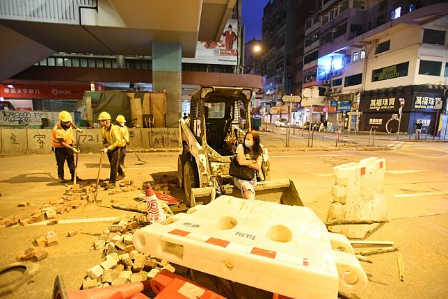 一名女子坐在剷車斗上圖止工作清理。丁志雄攝
