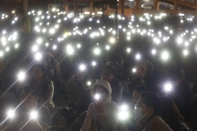 市民集會時亮起手機燈光。(何天成攝)