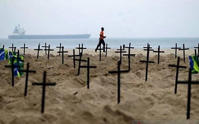 Seorang pria berlari melewati ratusan makam yang digali oleh aktivis LSM Rio de Paz di Pantai Copacabana, menyimbolkan warga yang meninggal dunia akibat penyakit  Covid-19 di Rio de Janeiro, Brasil, Kamis (11/6/2020)./Antara-Reuters