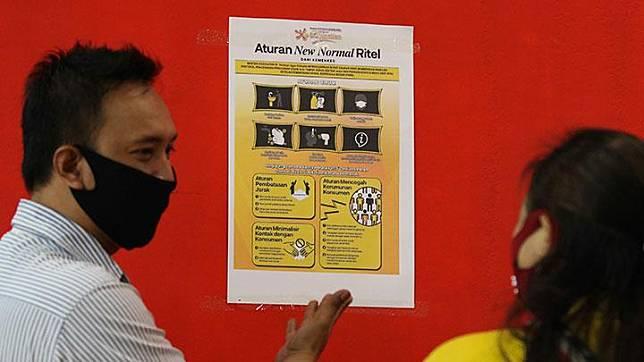 Pegawai swalayan Carrefour menunjukkan poster 'Aturan New Normal Ritel' kepada pengunjung usai ditempel di BG Junction, Surabaya, Rabu, 27 Mei 2020. Penempelan poster itu agar pengunjung memahami protokol pencegahan penularan COVID-19 saat mengunjungi pusat perbelanjaan. ANTARA/Didik Suhartono