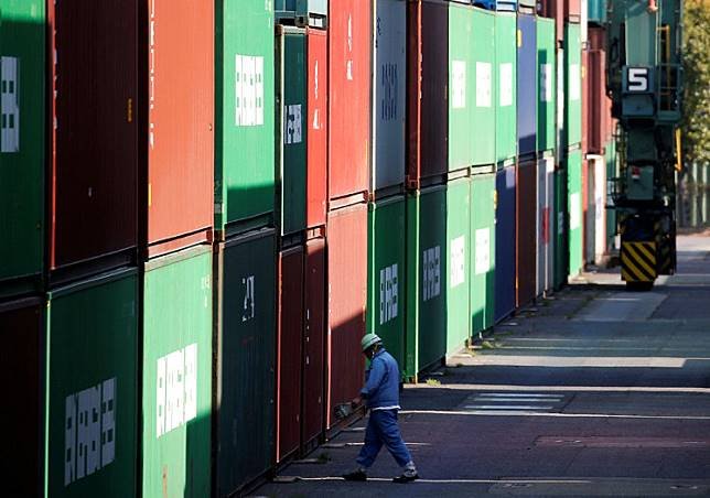 A stevedore walks between shipping containers at a port in Tokyo.