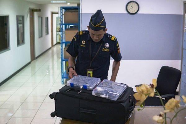 Seorang petugas bea cukai sedang memeriksa bawaan TM berupa 16 ekor kadal dalam kotak.