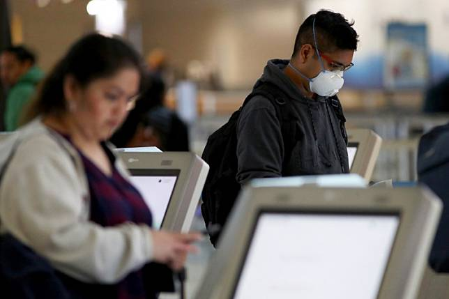 A passenger checks in for an American Airlines in Terminal D at Dallas/Fort Worth International Airport (DFW) on March 13, 2020 in Dallas, Texas.