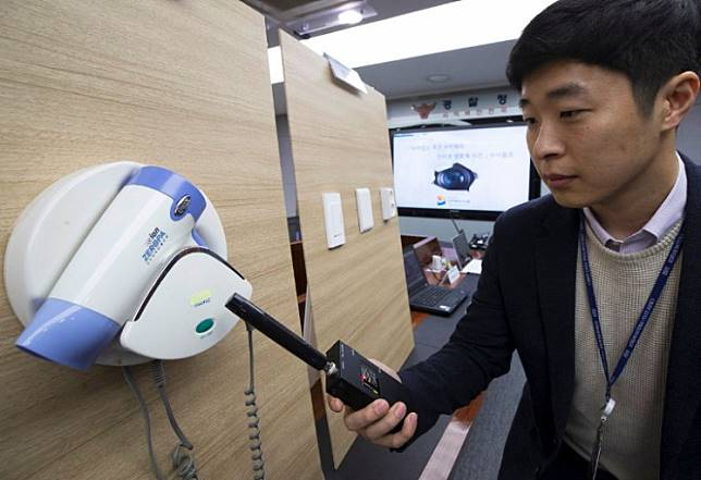 This picture taken on March 20, 2019 shows a police official testing a detector in front of a hidden mini-camera installed in a hair-dryer holder as South Korean police talk to the media about the latest spycam-related crime at the Korean National Police Agency in Seoul. More than 800 South Korean couples were livestreamed having sex in love motels, Seoul police said Thursday in one of the largest-scale and most intrusive examples yet of the country's spycam epidemic.