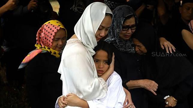 Bunga Citra Lestari memeluk anaknya Noah Sinclair yang saat prosesi pemakaman Ashraf Sinclair di kompleks pemakaman San Diego Hills, Karawang, Jawa Barat, Selasa (18/2). [Suara.com/Angga Budhiyanto]