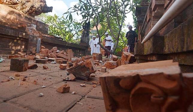 Pemuka agama Hindu memantau kerusakan pada bagian candi yang runtuh akibat gempa di Pura Lokanatha, Denpasar, Bali, Selasa, 16 Juli 2019. Gempa yang mengguncang Bali pada 6 skala richter pukul 08.18 Wita tersebut tidak menimbulkan korban jiwa tapi sejumlah bangunan di beberapa kawasan di Bali mengalami kerusakan. ANTARA