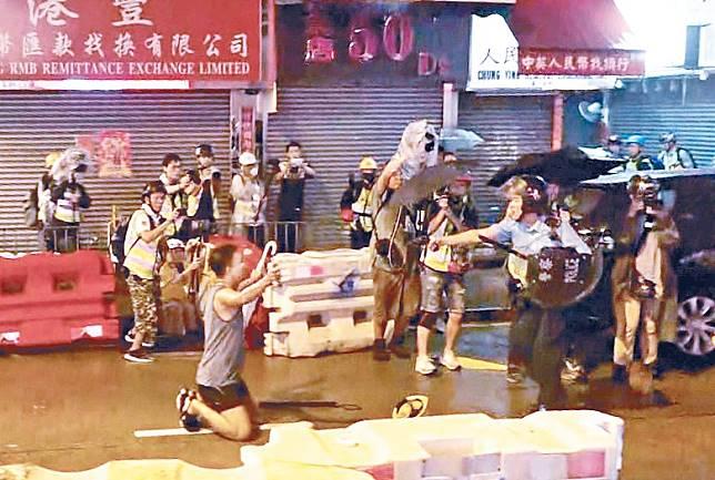 街坊跪在擎槍警員前高叫不要開槍。(黃劍能攝)