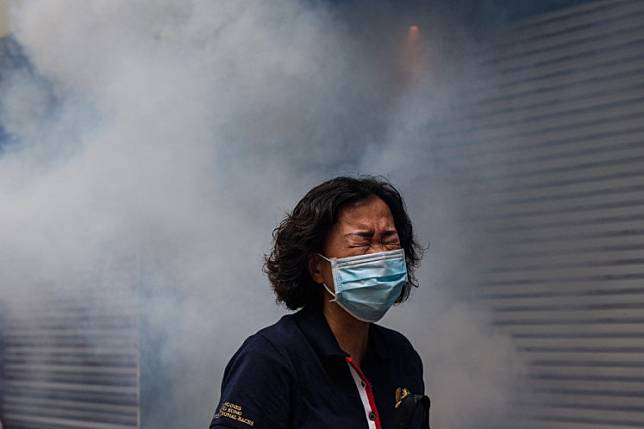 A woman reacts after riot police fired tear gas to disperse protesters taking part in a pro-democracy rally against a proposed new security law in Hong Kong on May 24, 2020. Police fired tear gas and water cannon at thousands of Hong Kong pro-democracy protesters who gathered on May 24 against a controversial security law proposed by China, in the most intense clashes in months.