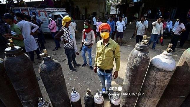 Orang-orang menunggu untuk mengisi ulang tabung oksigen medis mereka untuk pasien Covid-19 di stasiun pengisian oksigen di Allahabad India pada 24 April 2021.