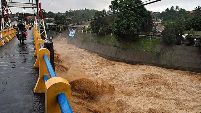 Pengendara motor melintas di atas jembatan saat tinggi muka air sungai Ciliwung naik di Bendung Katulampa, Kota Bogor, Rabu, 1 Januari 2020. Tinggi Muka Air di Katulampa menjadi pemandangan bagi warga di sekitarnya. ANTARA/Arif Firmansyah