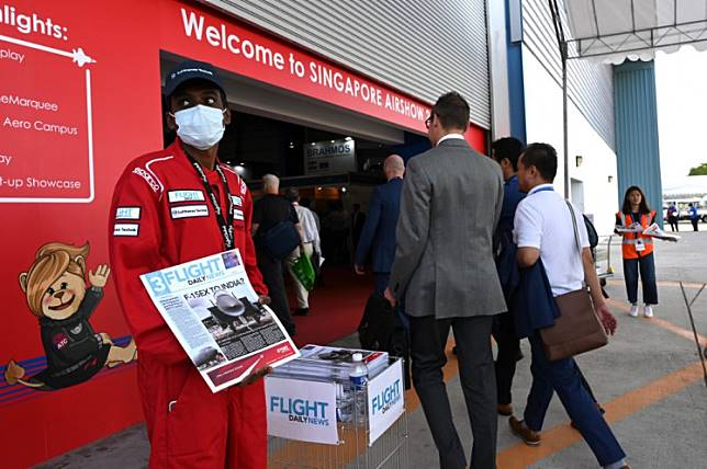 A promotional staff wearing protective face mask distributes flight magazines to visitors as they enter the hall to the Singapore Airshow in Singapore on February 13, 2020. (Photo by ROSLAN RAHMAN / AFP)