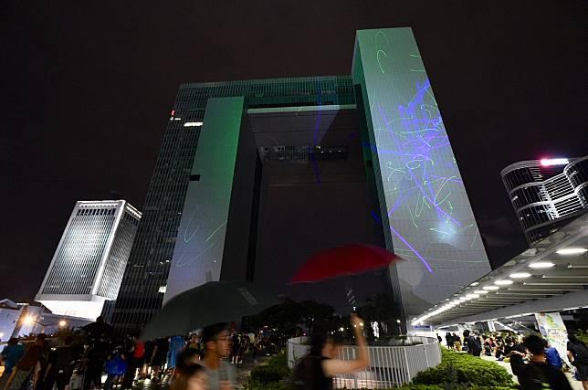 小圖為示威者以鐳射光線照向政府總部。