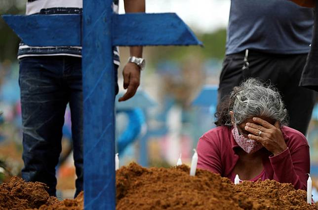 A woman reacts during a mass burial of people who passed away due to the COVID-19, at the Parque Taruma cemetery in Manaus, Brazil, May 26, 2020.
