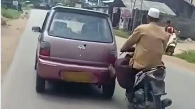 Pemotor yang sanggup dorong mobil sambil berkendara. (Facebook)