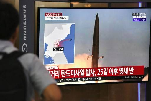A man watches a television news screen showing file footage of a North Korean missile launch, at a railway station in Seoul on July 31, 2019. Pyongyang fired two ballistic missiles on July 31, Seoul said, days after a similar launch that the nuclear-armed North described as a warning to the South over planned joint military drills with the United States.