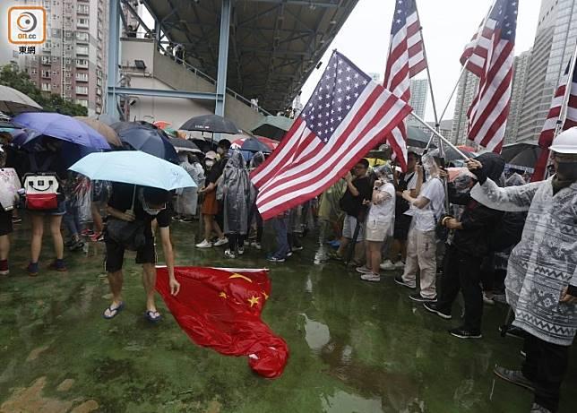 示威者手持美國國旗,五星旗則被放於地下。(何天成攝)