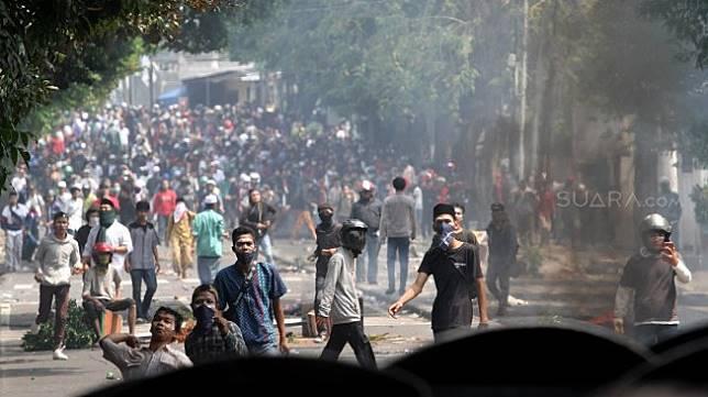 Bentrok antara massa dan pihak kepolisian di Jalan Slipi 1, Jakarta, Rabu (22/5). Massa yang memprotes KPU dan Bawaslu mengepung sejumlah titik di Kawasan Slipi, Petamburan, Kemanggisan dan Tanah Abang yabg berujung kerusuhan. [Suara.com/Arief Hermawan P]